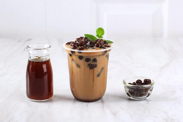 Tajwańska lodowa czekolada mleczna lub kawa z perłami boba tapioca na wierzchu z listkiem mięty jako dekoracją. przy drewnianym stole