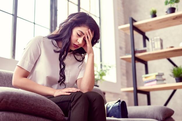 Tak bardzo wyczerpany. smutna zmęczona kobieta trzymająca się za czoło, czując się bardzo wyczerpana
