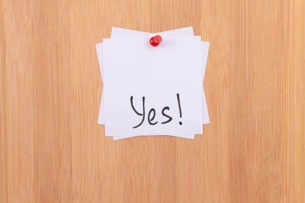 Tak białe karteczki samoprzylepne z napisanym słowem tak przypięte do drewnianej tablicy dyskusyjnej