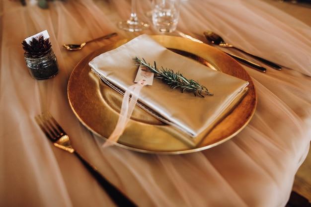 Tak dobra zastawa stołowa na stole w złotych odcieniach