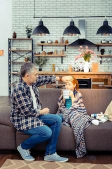 Tak gorąco. miły, przystojny ojciec dotyka czoła jej córki, jednocześnie opiekując się nią podczas choroby