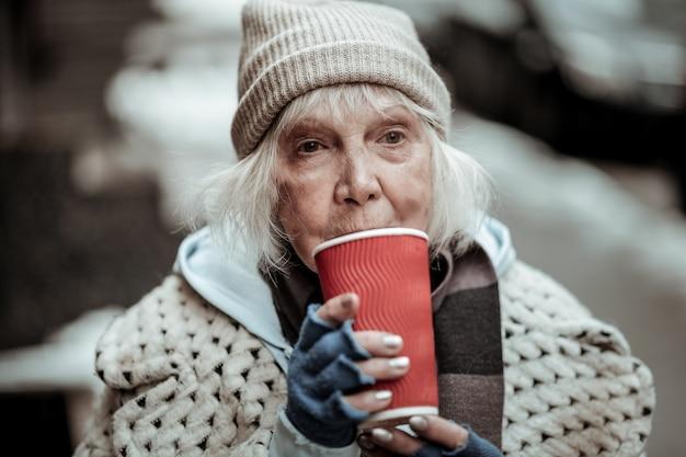Tak gorąco. smutna biedna kobieta stojąca z filiżanką herbaty podczas picia