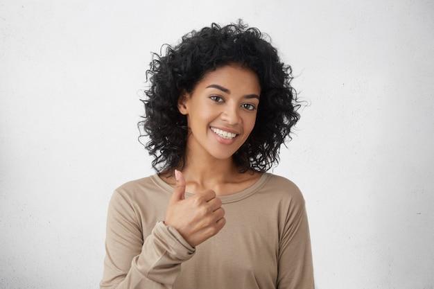 Tak jest lepiej. wesoły entuzjastyczny piękna młoda kobieta rasy mieszanej z kręconymi włosami pokazując kciuk do góry gest