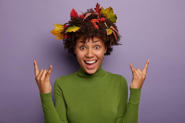 Tak, jest super! rozradowana kobieta z włosami afro ozdobionymi kolorowymi liśćmi, cieszy się jesienią, podnosi ręce i pokazuje rock and rolla, ubrana swobodnie, czuje się naładowana energią odizolowaną na fioletowej ścianie