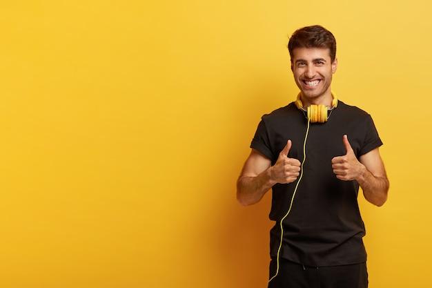 Tak, lubię tę muzykę! pozytywny hipster wystawia kciuki do góry, pokazuje gestem, wyraża dobre emocje