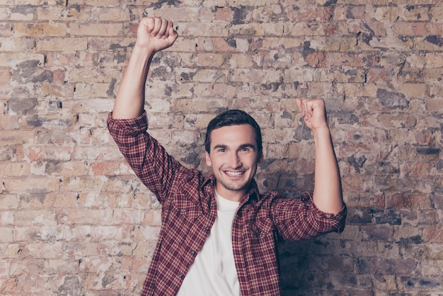 Tak! młody szczęśliwy człowiek triumfujący z podniesionymi pięściami