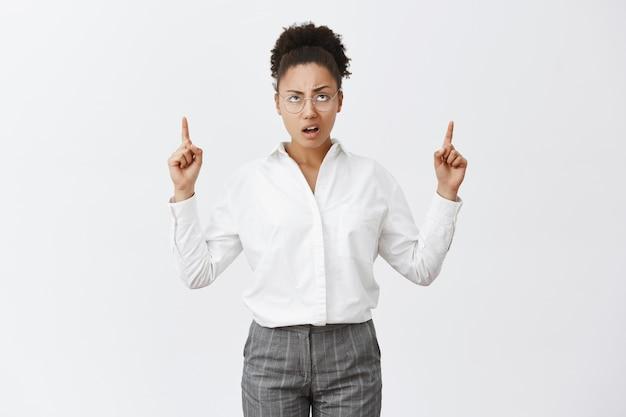 Tak nieudolne. portret niezadowolonej, niezadowolonej i rozczarowanej afroamerykańskiej przedsiębiorczyni w okularach i spodniach, marszczącej brwi, wskazującej i wpatrującej się w wątpliwość i nieszczęśliwą minę