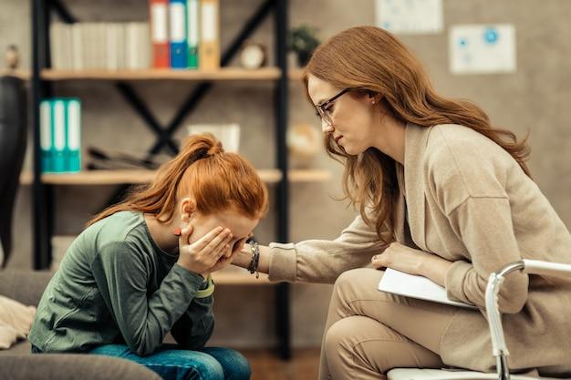 Tak przygnębiony. nieszczęśliwa młoda dziewczyna zakrywa swoje miejsce podczas płaczu