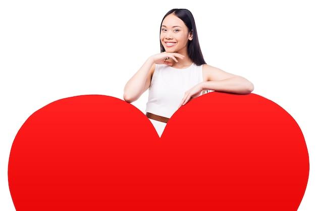 Tak samo cię kocham! piękna młoda azjatka w ładnej sukience patrząca na kamerę opartą na ogromnej walentynkowej kartce w kształcie serca i uśmiechnięta stojąc na białym tle