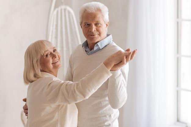 Tak samo jak wiele lat temu. radosna szczęśliwa para starszych stojących razem i tańcząca, wspominając swoją młodość