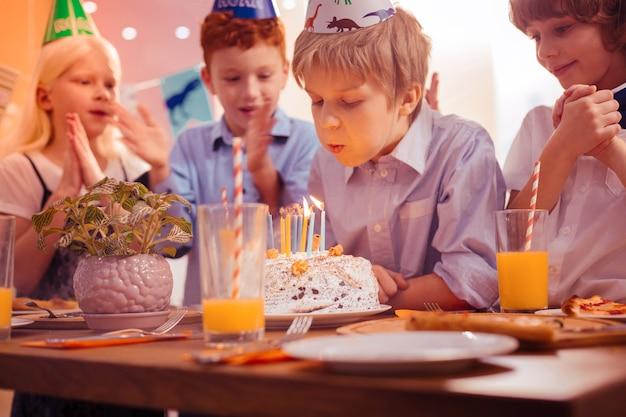 Tak skoncentrowany. pozytywnie zachwycone dzieciaki stojące obok koleżanki i ściskające dłonie