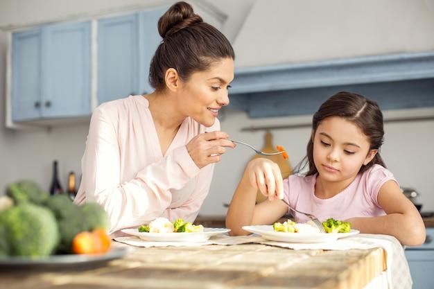 Tak smaczne. piękna szczęśliwa ciemnowłosa młoda mama uśmiecha się i je zdrowe śniadanie z córką i mamą karmiącą ją widelcem