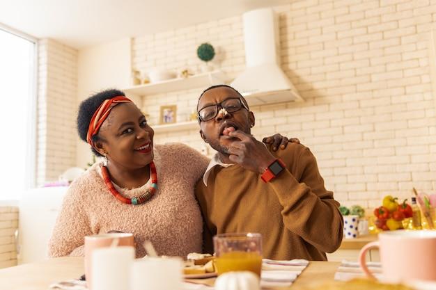 Tak smaczne. radosny, miły mężczyzna z kremem na nosie siedząc razem z żoną w kuchni