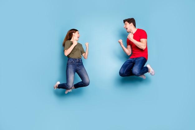 Tak, szczęśliwa wygrana! pełnowymiarowe zdjęcie profilowe z boku szalonego funky zachwyconego dwoje zamężnych ludzi skacze świętować zwycięstwo na loterii podnieść pięści krzyczeć nosić nowoczesny dżins izolowany niebieski kolor tło