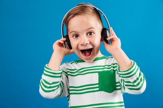 Tak szczęśliwy młody chłopak słucha muzyki przez słuchawki