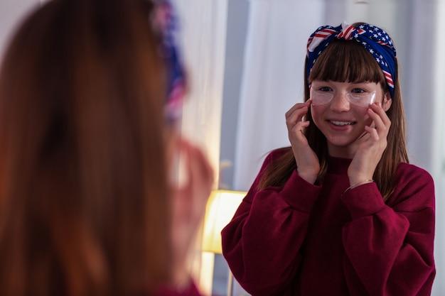Tak szczęśliwy. pozytywnie zachwycona uczennica wykonująca zabieg kosmetyczny spędzając weekend w domu
