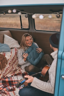 Tak szczęśliwy! widok z góry na przystojnego młodego mężczyznę grającego na gitarze dla swojej pięknej dziewczyny, siedząc w niebieskim mini vanie w stylu retro