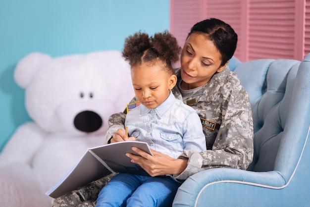 Tak to pisze się. troskliwa piękna kobieta pomaga córce odrabiać lekcje, gdy oboje siedzą na wygodnym krześle