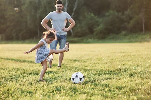 Tak to się dzieje. entuzjastyczny tata uczy córkę, jak grać w swoją ulubioną grę. to piłka nożna i nawet małe dziewczynki mogą w nią grać.