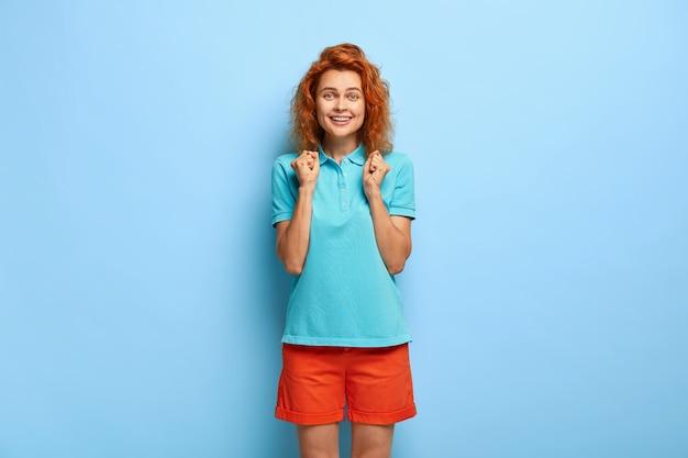 Tak, wreszcie sukces! radosna ładna młoda kobieta z lśniącą fryzurą świętuje słodki smak zwycięstwa