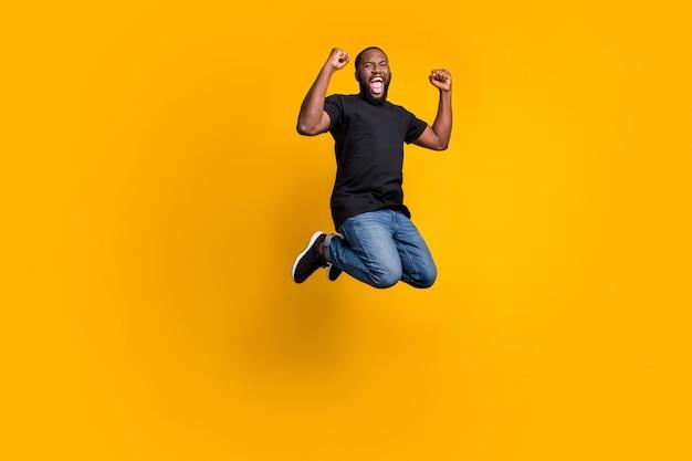 Tak, wygrywam! pełnowymiarowe zdjęcie zachwycony zabawny szalony afroamerykański facet świętuje zwycięstwo na loterii podskakuje pięści krzycz nosić t-shirt dżinsy na białym tle jasny kolor ściana