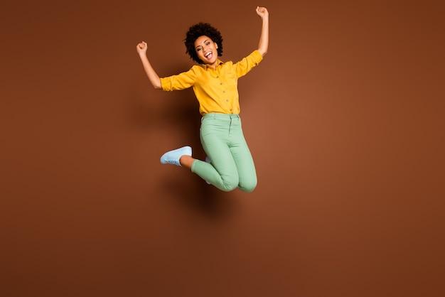 Tak! zdjęcie całego ciała zdumionej ciemnej skóry pani skaczącej wysoko świętującej wygraną na loterii podnoszenie pięści nosić żółtą koszulę zielone spodnie obuwie izolowany brązowy kolor