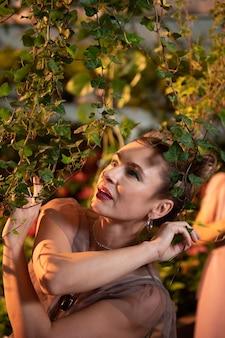 Tak zielony. piękna sympatyczna kobieta patrząca na gałęzie drzew podziwiając ich piękno