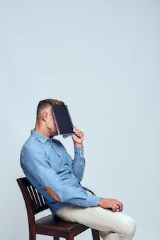Tak zmęczony widok z boku wyczerpanego brodatego mężczyzny w zwykłych ubraniach zakrywających twarz z