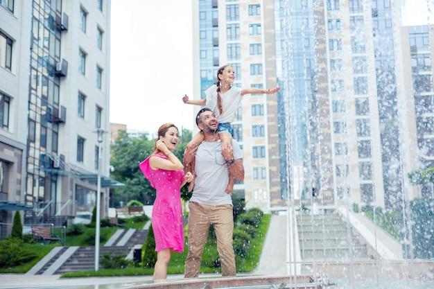Taka piękna. zachwycona szczęśliwa rodzina stojąca razem, patrząc na piękną fontannę