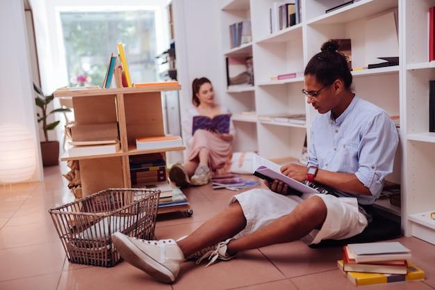 Taki dumny. skoncentrowany brunetka mężczyzna wpatrujący się w swoją książkę siedząc w półpozycji