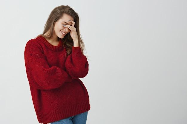 Taki głupi, ale taki słodki. studio strzałów atrakcyjnej stylowej kobiety w czerwonym luźnym swetrze robiącym twarz, trzymającej dłoń na oczach i uśmiechniętej, godzącej się z głupim poczuciem humoru chłopaka