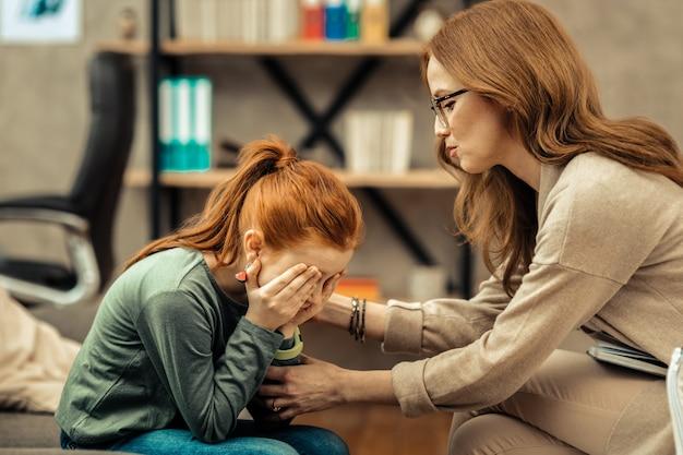 Taki smutny. ładna rudowłosa dziewczyna płacze, pokazując swoje emocje