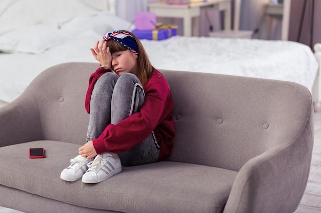 Taki smutny. zrelaksowana dziewczyna siedzi na kanapie i zakrywając twarz