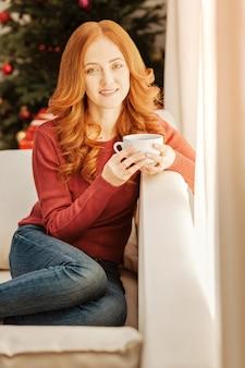 Taki wspaniały dzień. piękna ruda dojrzała pani w swobodnym siedzeniu na kanapie przy filiżance ciepłej herbaty.