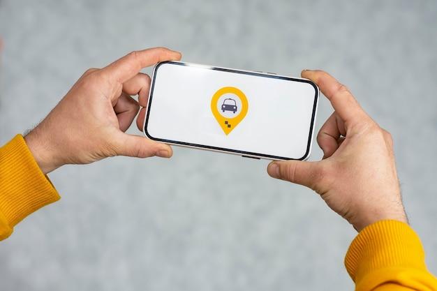 Taksówka online w twoim telefonie. mężczyzna trzyma smartfon z białym ekranem i ikoną geolokalizacji i lokalizacji taksówki.