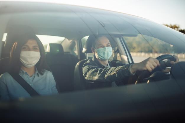 Taksówkarz ubrany w sterylną maskę medyczną trzyma ręce na kierownicy.
