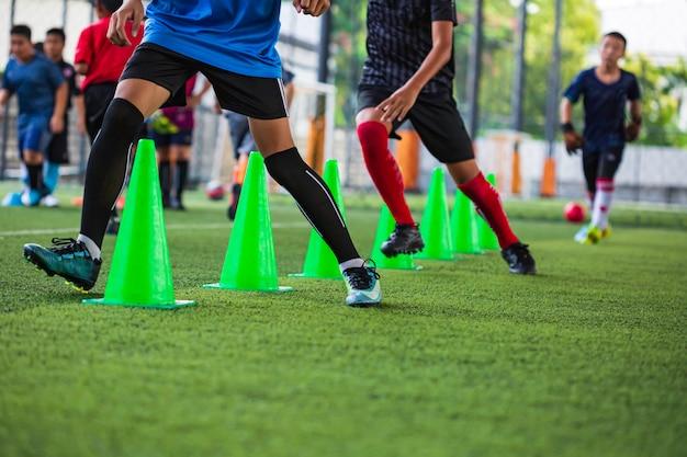 Taktyka piłki nożnej na boisku ze stożkiem do treningu umiejętności biegania dzieci w akademii piłkarskiej