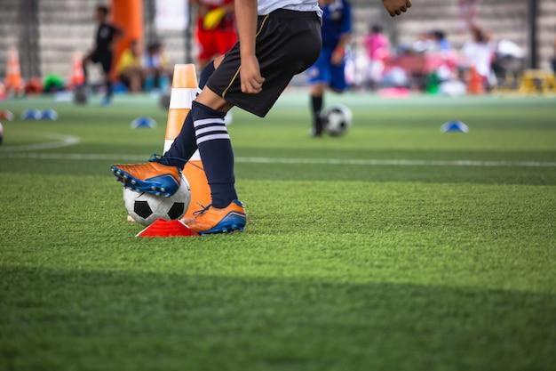 Taktyka piłki nożnej na boisku ze stożkiem do treningu w tle trening dzieci w akademii piłkarskiej