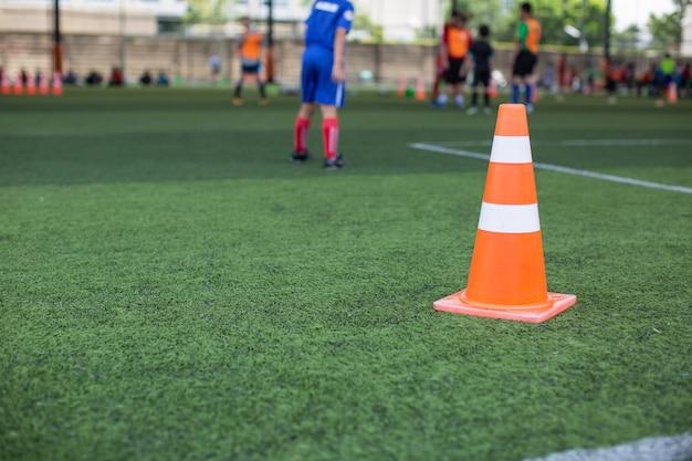 Taktyka piłki nożnej na boisku ze stożkiem na tle treningowym trening dzieci w akademii piłkarskiej