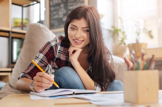 Talent i kreatywność. piękna radosna szczęśliwa kobieta trzyma ołówek i uśmiecha się podczas rysowania obrazu w swoim zeszycie