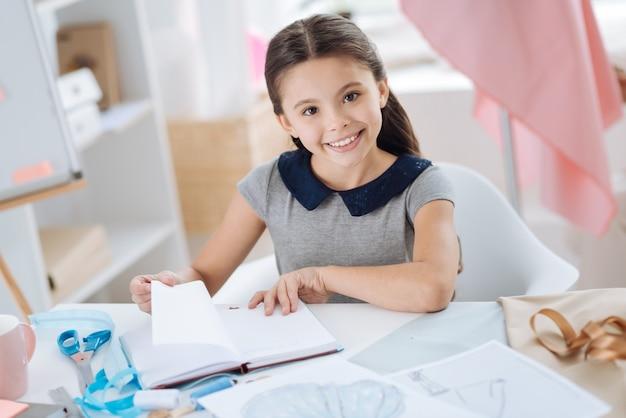 Talent i kreatywność. pozytywna miła kreatywna dziewczyna trzyma notes i przewraca stronę podczas pracy nad projektowaniem ubrań