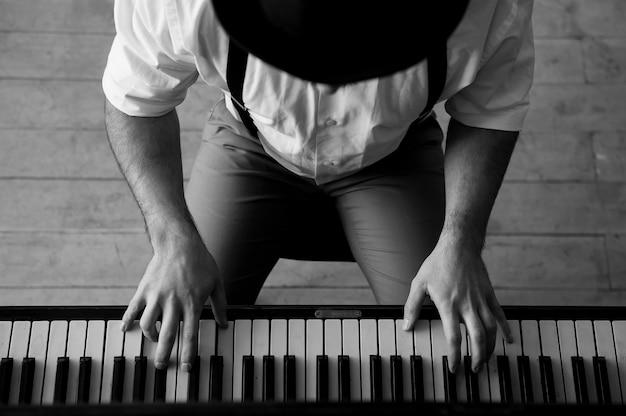 Talent i wirtuozeria. czarno-biały obraz z góry przedstawiający człowieka grającego na pianinie