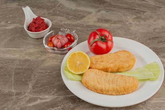 Talerz bryłek pomidora, cytryny i kurczaka.