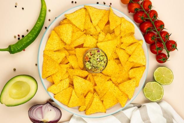 Talerz chipsów kukurydzianych nachos z guacamole i dodatkami z czerwonej cebuli, papryki awoka i pomidorów