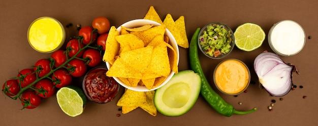 Talerz chipsów kukurydzianych nachos z sosami i dodatkami, czerwoną cebulą, avacado, papryką i pomidorami.