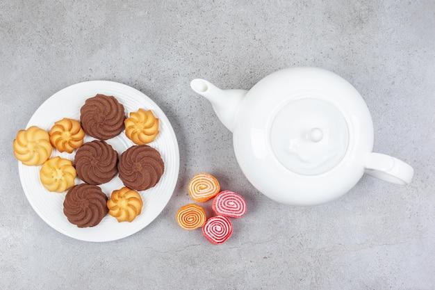 Talerz ciasteczek obok białego czajniczka i mała paczka marmolad na marmurowej powierzchni.