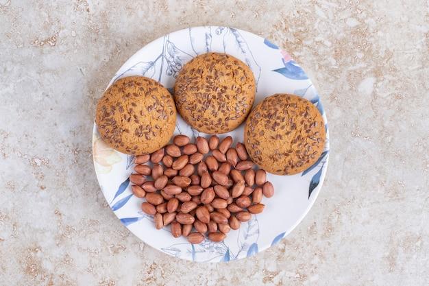 Talerz ciasteczek owsianych i ziaren orzeszków ziemnych na powierzchni marmuru.