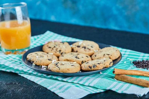 Talerz ciasteczek z kawałkami czekolady i szklankę soku pomarańczowego na ciemnym stole z cynamonem
