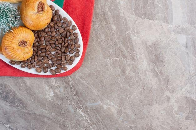 Talerz ciastek i ziaren kawy z figurką drzewa na marmurze.