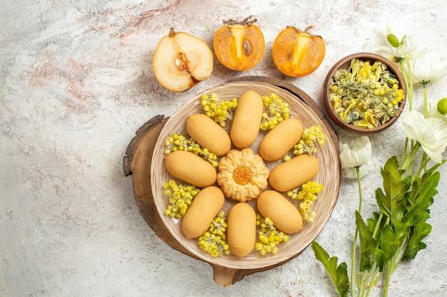 Talerz ciastek na drewnianym talerzu i miska ziół i pół gruszki, palmy i kwiatów